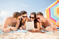 Group of smiling people with tablet pc on beach. Summer, holidays, vacation, technology and happy people concept - group of smiling people in sunglasses with stock photos