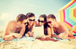 Group of smiling people with tablet pc on beach. Summer, holidays, vacation, technology and happy people concept - group of smiling people in sunglasses with royalty free stock photos
