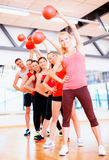Group of smiling people working out with ball Stock Images