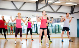 Group of smiling people working out with barbells. Fitness, sport, training, gym and lifestyle concept - group of smiling people working out with barbells in the Royalty Free Stock Images