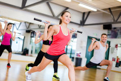 Group of smiling people working out with barbells. Fitness, sport, training, gym and lifestyle concept - group of smiling people working out with barbells in the Royalty Free Stock Photo