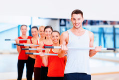Group of smiling people working out with barbells. Fitness, sport, training, gym and lifestyle concept - group of smiling people working out with barbells in the Stock Photos