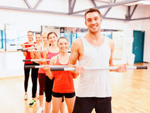 Group of smiling people working out with barbells Stock Image