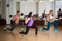 Group of smiling people working out with barbells Stock Photos