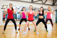Group of smiling people working out with barbells. Fitness, sport, training, gym and lifestyle concept - smiling trainer in front of the group of people working Royalty Free Stock Image