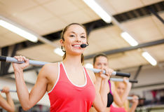 Group of smiling people working out with barbells. Fitness, sport, training, gym and lifestyle concept - smiling trainer in front of the group of people working Stock Photo