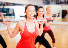 Group of smiling people working out with barbells. Fitness, sport, training, gym and lifestyle concept - smiling trainer in front of the group of people working Royalty Free Stock Photo