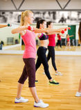 Group of smiling people working out with dumbbells Royalty Free Stock Photos