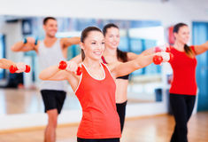 Group of smiling people working out with dumbbells Royalty Free Stock Photo