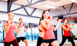 Group of smiling people working out with dumbbells Stock Photo