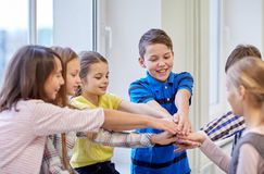 Group of smiling school kids putting hands on top Royalty Free Stock Images
