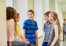 Group of smiling school kids talking in corridor Royalty Free Stock Photography