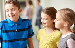 Group of smiling school kids talking in corridor Royalty Free Stock Photo