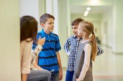 Group of smiling school kids talking in corridor. Education, elementary school, children, break and people concept - group of smiling school kids talking in stock images
