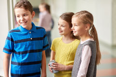 Group of smiling school kids talking in corridor Royalty Free Stock Images