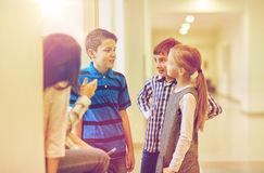 Group of smiling school kids talking in corridor Royalty Free Stock Photo