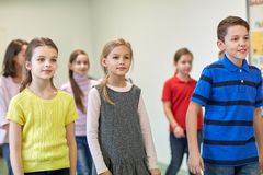 Group of smiling school kids walking in corridor Stock Photo