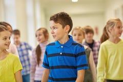 Group of smiling school kids walking in corridor Stock Image