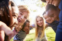 Group of smiling schoolchildren lean in to camera embracing stock photography