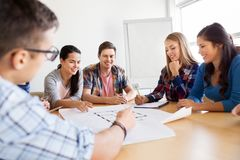 Group of smiling students with blueprint stock photos