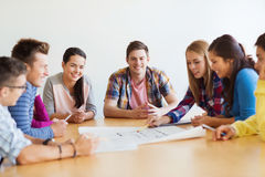 Group of smiling students with blueprint Stock Photo