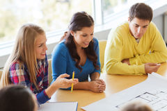 Group of smiling students with blueprint Stock Images