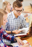 Group of smiling students with books. Education, high school, teamwork and people concept - group of smiling students with notebooks and book writing in lecture Royalty Free Stock Images