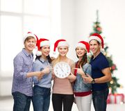 Group of smiling students with clock showing 12. Education, christmas, happiness and people concept - group of smiling students in santa helper hats with clock Royalty Free Stock Photos