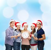 Group of smiling students with clock showing 12 Stock Photography