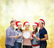 Group of smiling students with clock showing 12 Royalty Free Stock Photography
