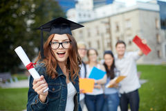 Group of smiling students with diploma and folders. Education, graduation and people concept - group of smiling students in mortarboard with diploma and school Royalty Free Stock Images