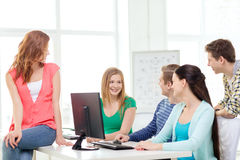 Group of smiling students having discussion. Education, technology, school and people concept - group of smiling students having discussion in computer class at Royalty Free Stock Photo