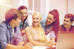 Group of smiling students with laptop at school Stock Photo