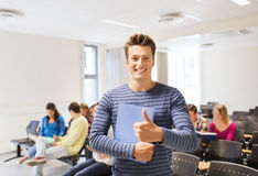 Group of smiling students in lecture hall. Education, high school, gesture and people concept - group of smiling students with notepads showing thumbs up in Royalty Free Stock Photo