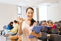 Group of smiling students in lecture hall. Education, high school, teamwork and people concept - group of smiling students with notepads showing ok gesture in Stock Photography