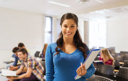 Group of smiling students in lecture hall. Education, high school, teamwork and people concept - group of smiling students with notepads sitting in lecture hall Stock Photo