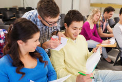 Group of smiling students in lecture hall. Education, high school, teamwork and people concept - group of smiling students with notepads sitting in lecture hall Royalty Free Stock Image