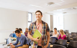 Group of smiling students in lecture hall. Education, high school, teamwork and people concept - group of smiling students with notepads sitting in lecture hall Royalty Free Stock Images