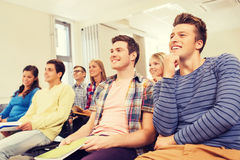 Group of smiling students in lecture hall. Education, high school, teamwork and people concept - group of smiling students with notepads sitting in lecture hall Stock Image