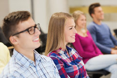 Group of smiling students in lecture hall. Education, high school, teamwork and people concept - group of smiling students sitting in lecture hall Stock Image