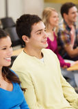 Group of smiling students in lecture hall. Education, high school, teamwork and people concept - group of smiling students sitting in lecture hall Stock Images