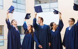 Group of smiling students in mortarboards. Education, graduation and people concept - group of smiling students in gowns waving mortarboards outdoors Stock Photography