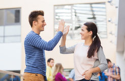 Group of smiling students outdoors. Friendship, gesture, education and people concept - group of smiling students outdoors making high five Royalty Free Stock Photos
