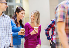 Group of smiling students with paper coffee cups. Education, high school, friendship, drinks and people concept - group of smiling students with paper coffee Royalty Free Stock Images