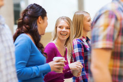 Group of smiling students with paper coffee cups Royalty Free Stock Images