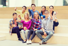 Group of smiling students with paper coffee cups. Education, high school, friendship, drinks and people concept - group of smiling students with paper coffee Stock Images