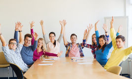 Group of smiling students raising hands in office Stock Photos