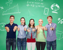 Group of smiling students showing thumbs up. Education, friendship, gesture, and people concept - group of smiling students standing and showing thumbs up over royalty free stock photos