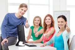 Group of smiling students showing thumbs up. Education, technology, school and people concept - group of smiling students showing thumbs up in computer class at Royalty Free Stock Images