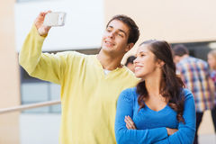 Group of smiling students with smartphone outdoors Stock Photo